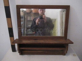 wall mirror in a wooden frame with a shelf